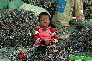在電子廢棄物堆當中生活的小孩